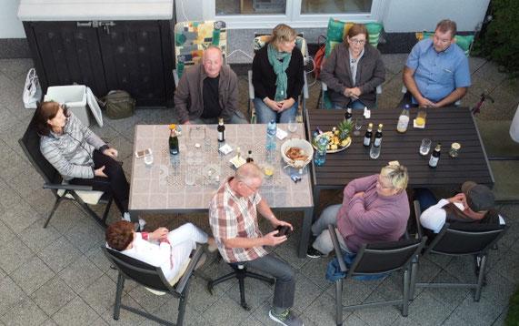 9 Menschen sitzen um einen Tisch herum. Gläser, Flaschen und Essen steht auf dem Tisch.  Die Menschen unterhalten sich.