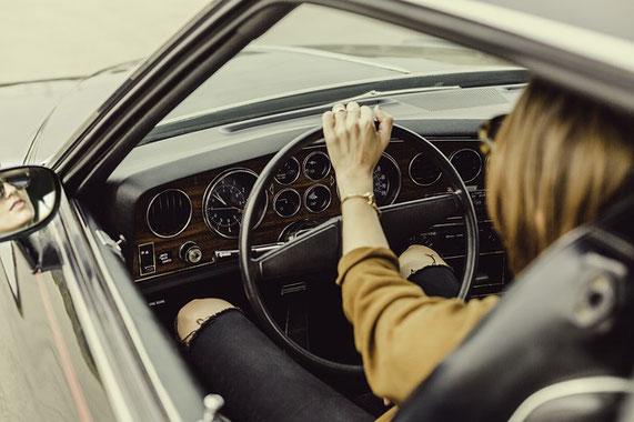 Frau sitz in Auto. Blick durch die offene Scheibe des Autos