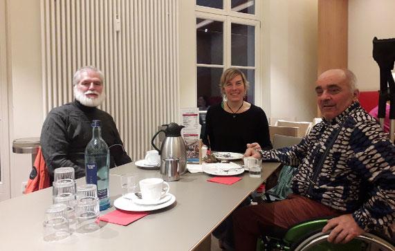 Zwei Männer (einer davon im Rollstuhl) und eine Frau sitzen an einem Tisch, trinken Kaffee, essen Kuchen und unterhalten sich