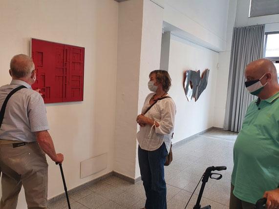 Zwei Männer und eine Frau stehen vor einem roten Kunstwerk welches an einer Wand hängt.