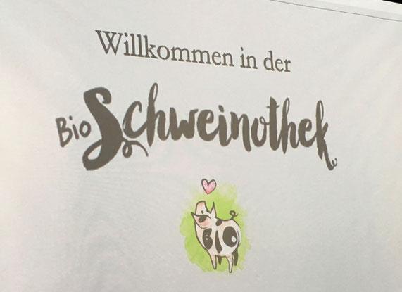 Foto. Text: Willkommen in der Schweinothek. Abgebildet wird ein kleines Schweinchen mit einem Herzz