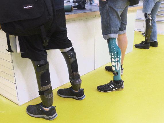 Foto: Männer mit Beinprothesen stehen vor einem Tisch