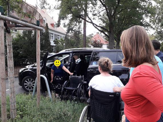 Eine Frau entlädt ihren Rollstuhl mittels eines Verladesystems aus ihrem schwarzen Auto.