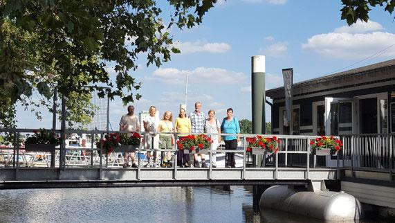 7 Menschen stehen mit lachenden Gesichtern auf einer Gangway zu einem Lokalboot im Schiersteiner Hafen in Mainz