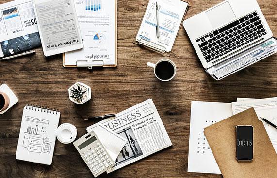 Foto: Schreibtisch mit Laptopp, Unterlagen und Kaffee