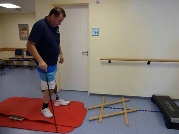 Mann mit Prothese und Stock läuft im Physiotherapieraum über eine Matte.