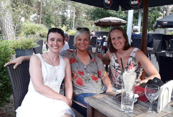 3 von beinamputation Betroffene Frauen sitzen in einem Cafe