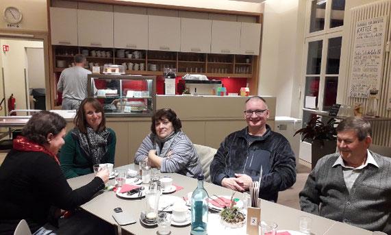 5 Menschen sitzen redend und lachend in einem Cafe am Tisch.