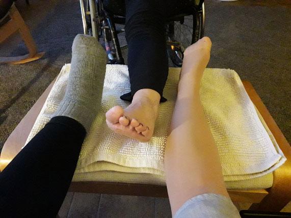 Drei Füße von Frauen liegen auf einem Hocker.