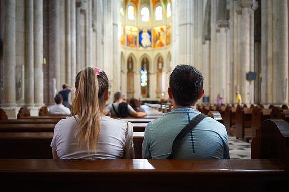 Ein Mann und eine Frau sitzen in einer Kirche