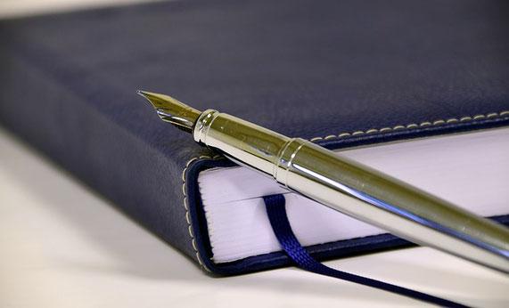 Ein blaues Notizbuch auf dem ein Füller liegt