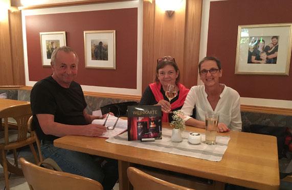 3 Menschen die in einer Gaststätte an einem Tisch sitzen und trinken und reden.