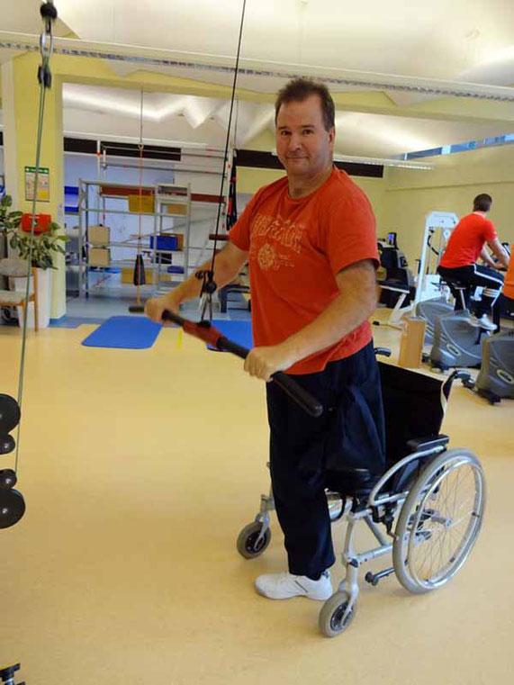 Mann steht auf einem Bein am Zuggerät in der Physiotherapie.