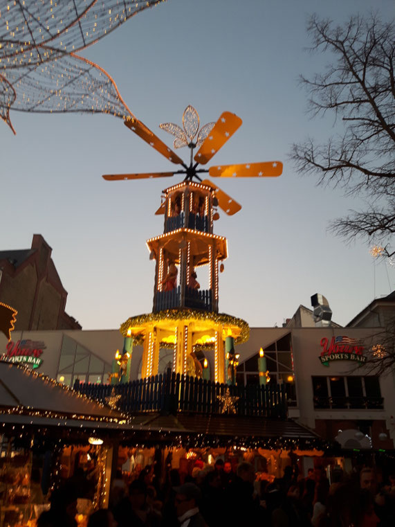 Weihnachtspyramide auf einem Weihnachsmarkt in Wiesbaden. Viele Menschen sind zu sehen.