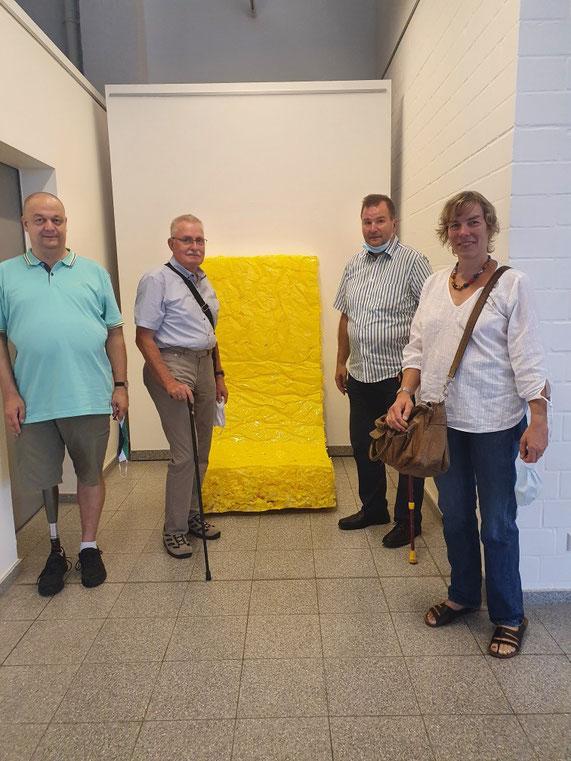 3 Männer und eine Frau mit Beinprothesen stehen vor einem gelben Kunstwerk in einer Galerie