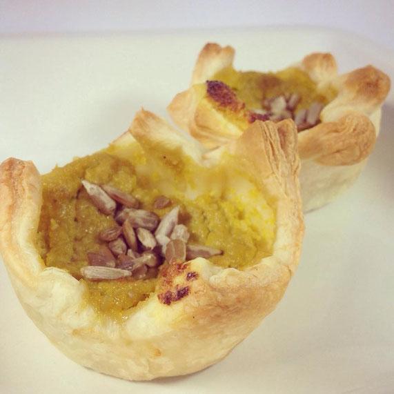 Blätterteig-Quiches gefüllt mit gelbem, mildem Paprika-Pesto, dekoriert mit Sonnenblumenkernen.