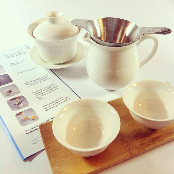 Das Teezubereitungsset im Überblick (aufgegossen wird hinten im Gaiwan, gefiltert im Pitcher und getrunken in den Schälchen). Das Faltblatt ist dabei gleichzeitig Anleitung als auch Informationsbroschüre für die beigelegten fünf Teesorten.