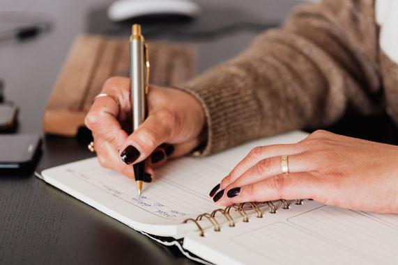 Frau schreibt Journal gegen Überforderung und Stress