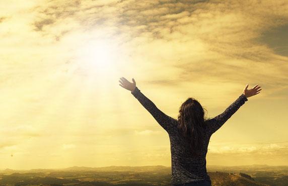 Femme brune qui écarte les bras au ciel. Le ciel est doré.