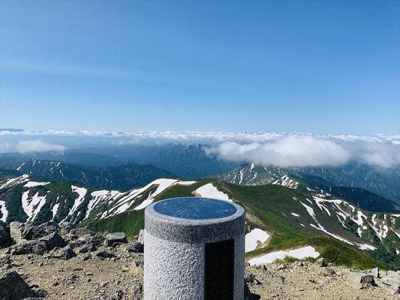 ▲山頂より平岩山方面。右奥の雲の上からまだたっぷり雪をかぶった飯豊連峰が頭をのぞかせる