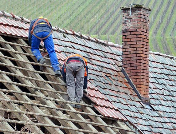 Reparatur eines alten Dachstuhls mit neuen Dachziegeln.