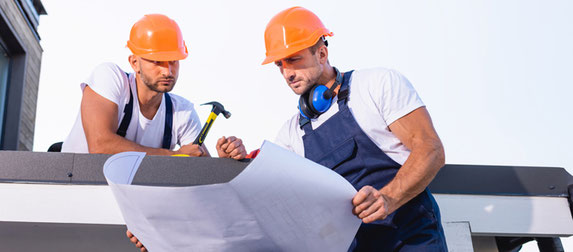 Zwei Männer mit Bauhelm schauen sich den Plan an.