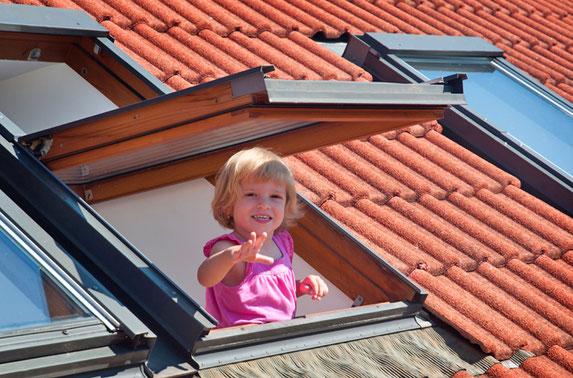 Mädchen schaut aus Dachfenster hinaus.