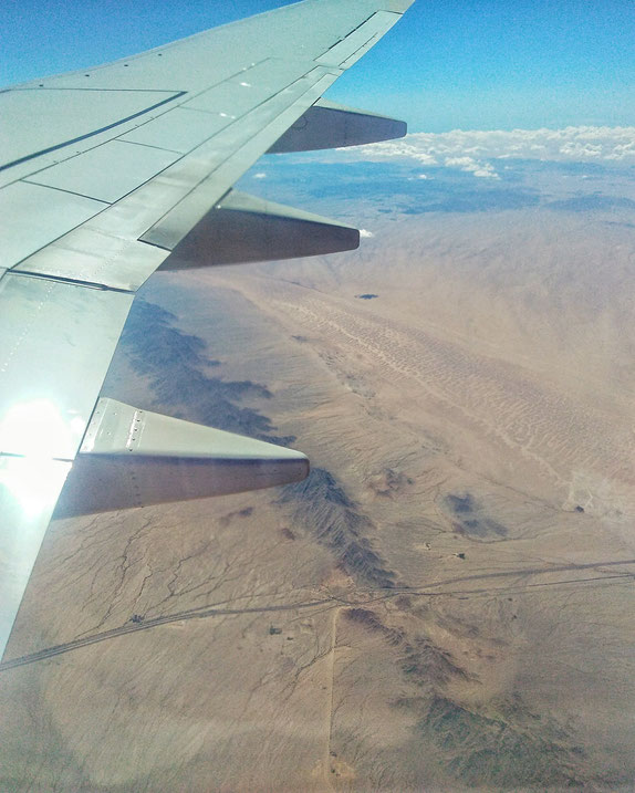 airplane wing over the desert