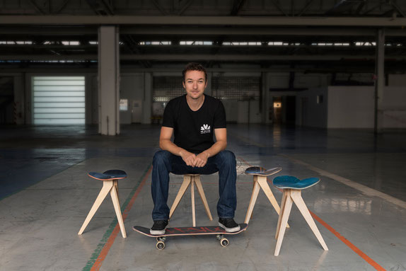 Skateboarddesigner and founder Florian Bürkle is sitting on his product Mister Wilson stool. Skateboarddesigner Florian Bürkle sitz auf seinem Produkt dem Skateboardhocker Mister Wilson.