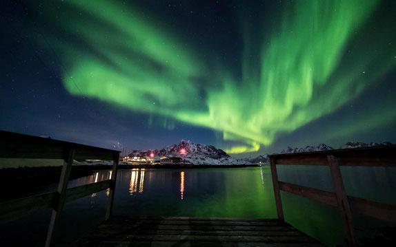 Grünes Nordlicht am Wasser mit Blick auf schneebedeckten Berg und einen Ort - XXLofoten Northern lights photo tour© Geir Nøtnes