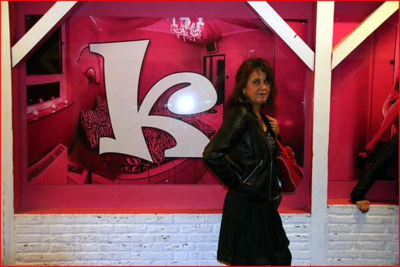 """Karin steht im Durchgang zum Lokal """"Zur Ritze"""" vor einem Plakat mit einem K."""