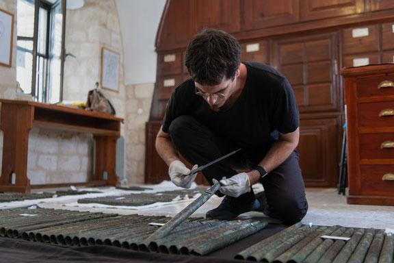 David Catalunya examining 12th-century organ pipes at the Terra Sancta Museum in Jerusalem