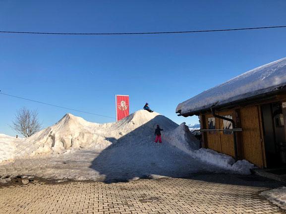Kinder erklimmen Schneehügel hinter traumhaftem Panorama