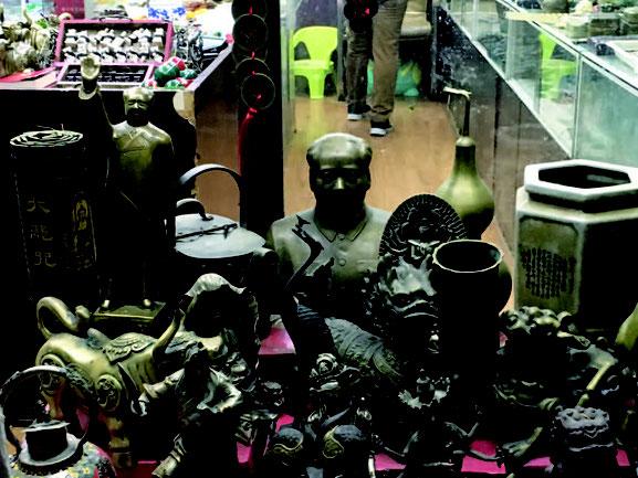 骨董屋で妖怪の人形と並ぶ毛沢東