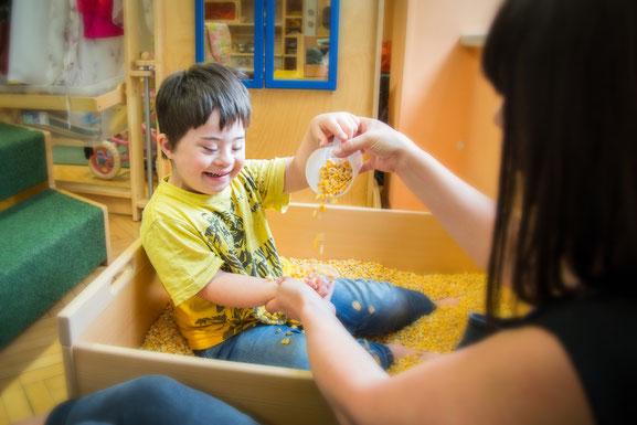 bub-down-syndrom-betreuerin-vinco-heilpädagogischer-kindergarten-maiskorn-spielen