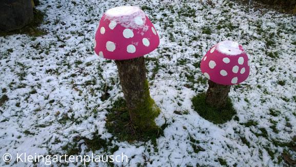 Kurze Baumstämme, darauf pink mit weißen Tupfen bemalte, umgedrehte Tonschalen, auf der Wiese liegt Schnee