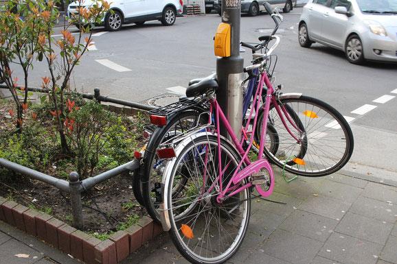 An Ampelanlagen angekettete Fahrräder versperren den Zugang zum Ampelknopf insbesondere für Rollstuhlfahrer und Kinderwagen.