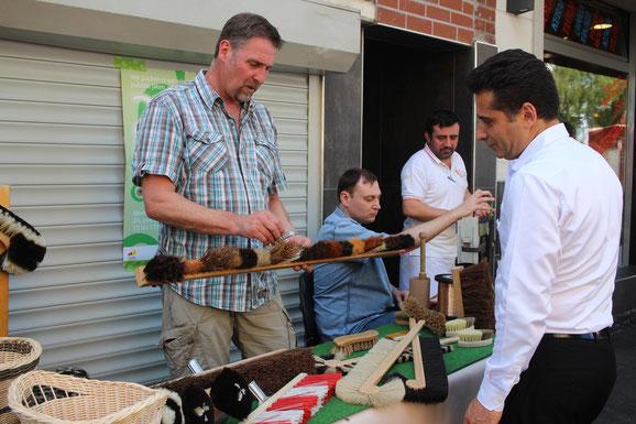 Am Stand der Blindenmanufaktur Kaniss erklärt der Werkstattleiter einem interessierten Mitarbeiter eines Restaurants, welche Materialien für einen Besen verwendet werden können. Im Hintergrund sieht man den Mitarbeiter an seinem Werktisch.