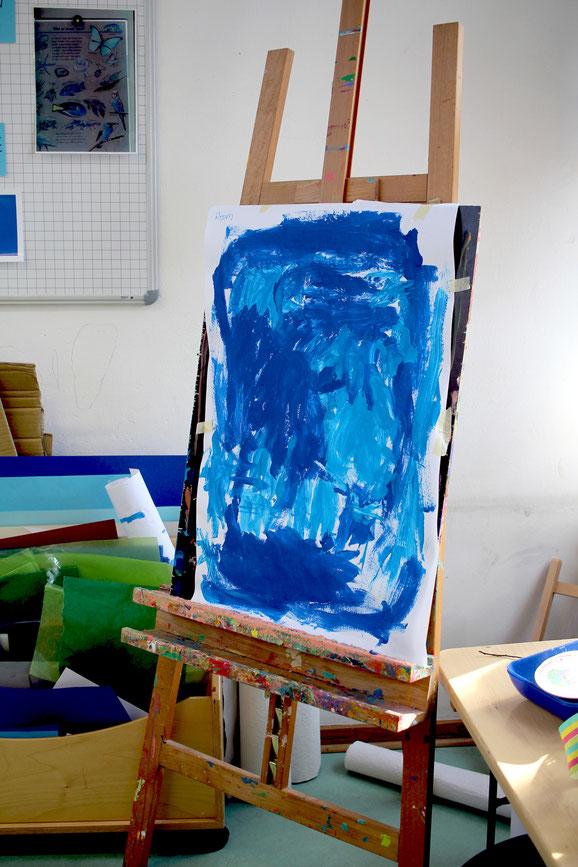 """Die Blaue Gruppe behandelt das Thema """"Leben im Wasser"""". Ein Kunstwerk auf der Kinder-Staffelei ist ganz in Blautönen gehalten."""