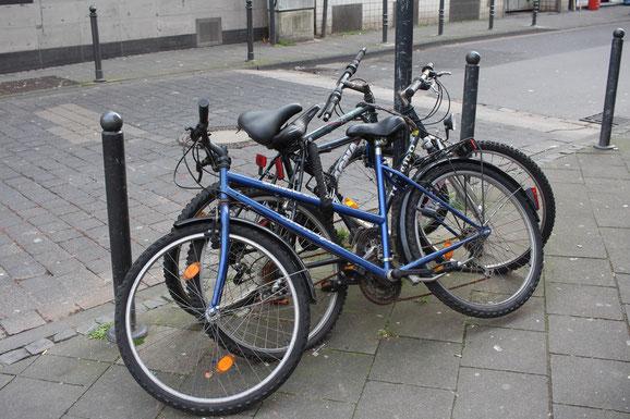 Abgestellte Fahrräder verstellen den Web für Fußgänger, Kinderwagen und Rollstuhlfahrer.