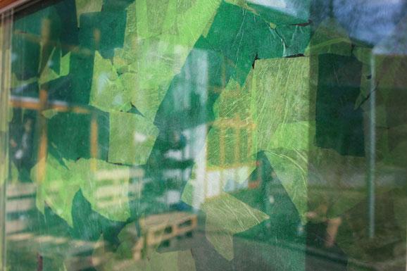 Der Fensterschmuck aus grünem Papier erinnert an Blätter eines Baums.