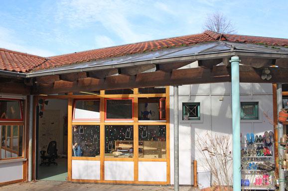 Der Holzveranda des Kindergartens hat Trapezdächer.