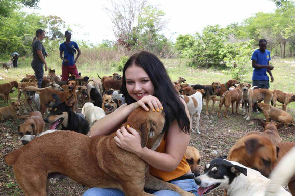 Happy girl on a hike with one hundred dogs at Montego Bay charity tour in Jamaica jungle