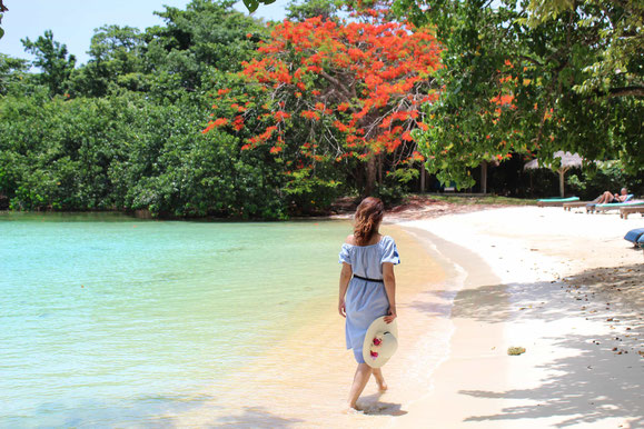 Woman on vacation walking along white sand beach at an excursion in Negril, Jamaica