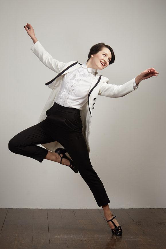 Tänzerin Ksenia Parkhatskaya winkelt ein Bein an und breitet die Arme aus