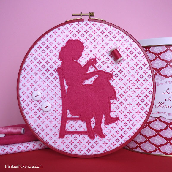 Red embroidery hoop with a pink seamstress silhouette