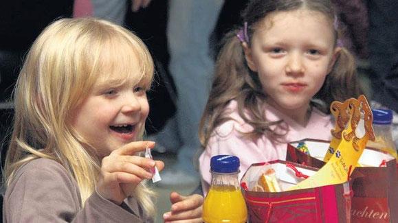 """Angelina und Debbie packen auf der Kinderweihnachtsfeier im Begegnungszentrum """"Soziale Stadt"""" im Kannenstieg ihre Geschenktüten aus, die der Weihnachtsmann ihnen gebracht hat. Foto: Robert Richter"""