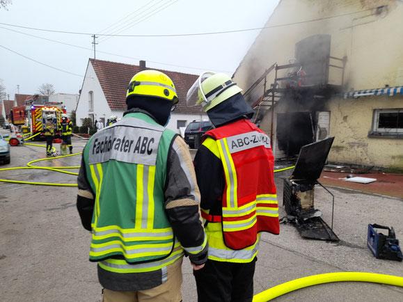 Führungskräfte des ABC-Zugs beurteilen vor der ausgebrannten Halle die Lage und besprechen die erforderlichen Maßnahmen.