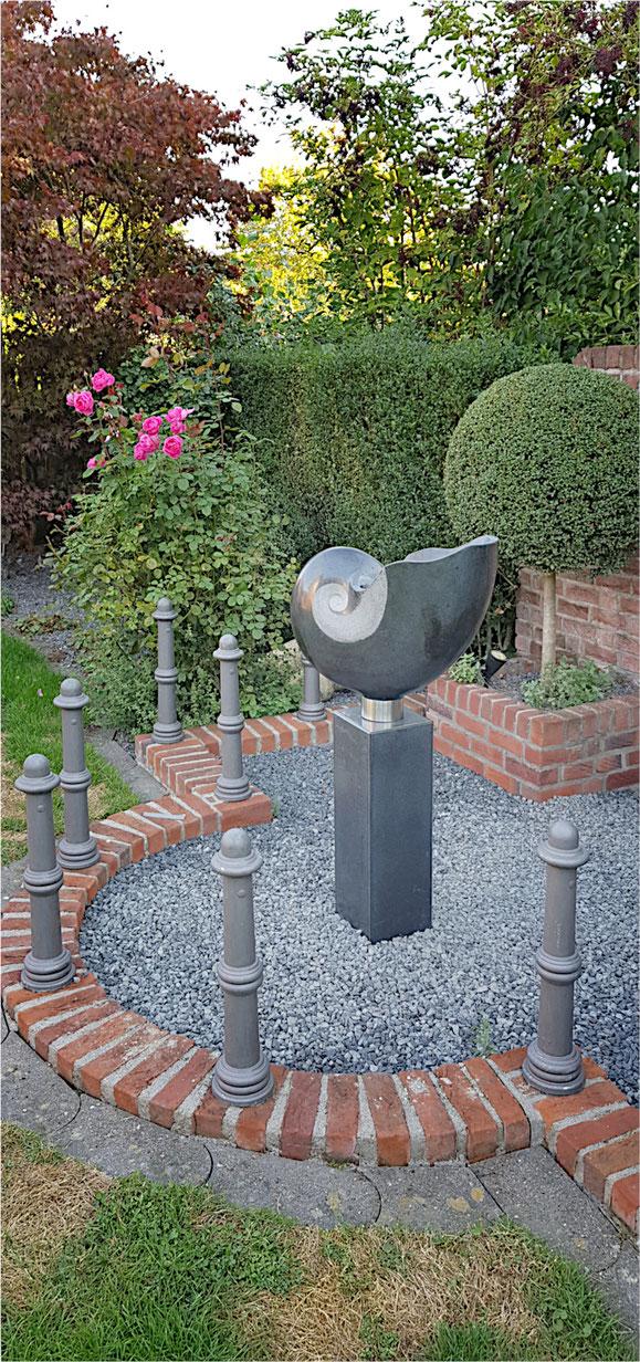 Nautilus aus schwarzem polierten Stein auf einer Säule montiert. Gartengestaltung einer besonderen Art.