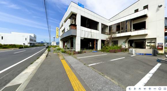 道路沿いに見る旧社屋、屋上のブルーの看板が8.5mに達した津波の高さを示す